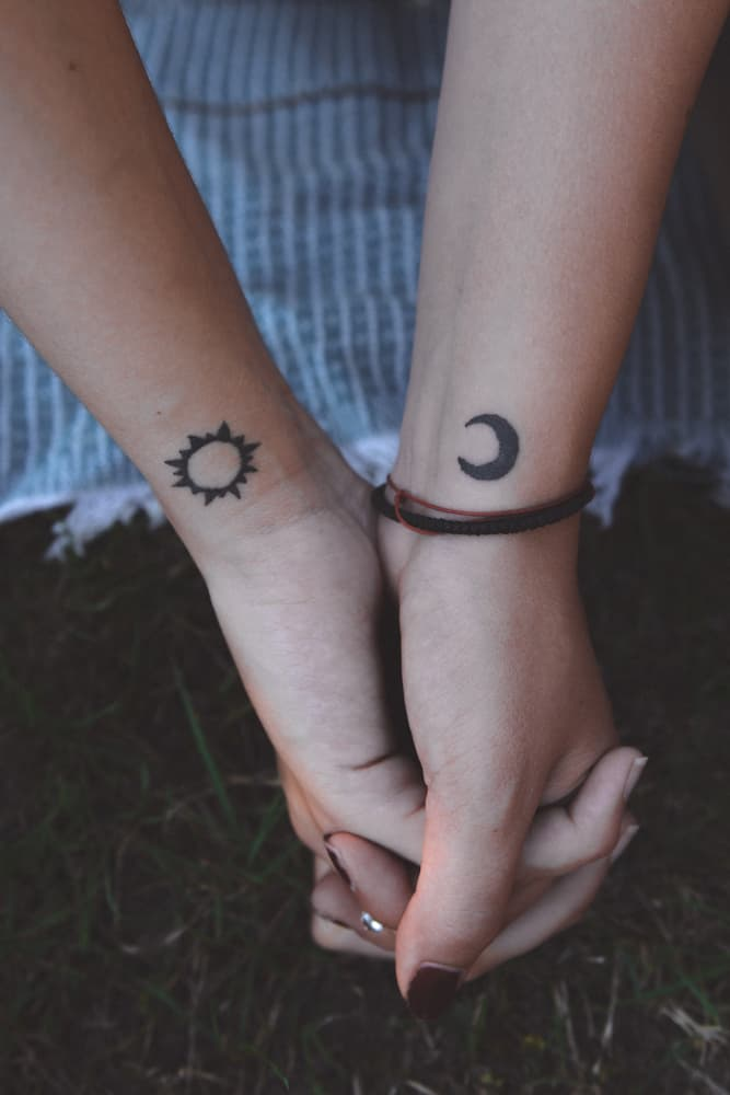 clasped hands with matching Sun and Moon tattoos