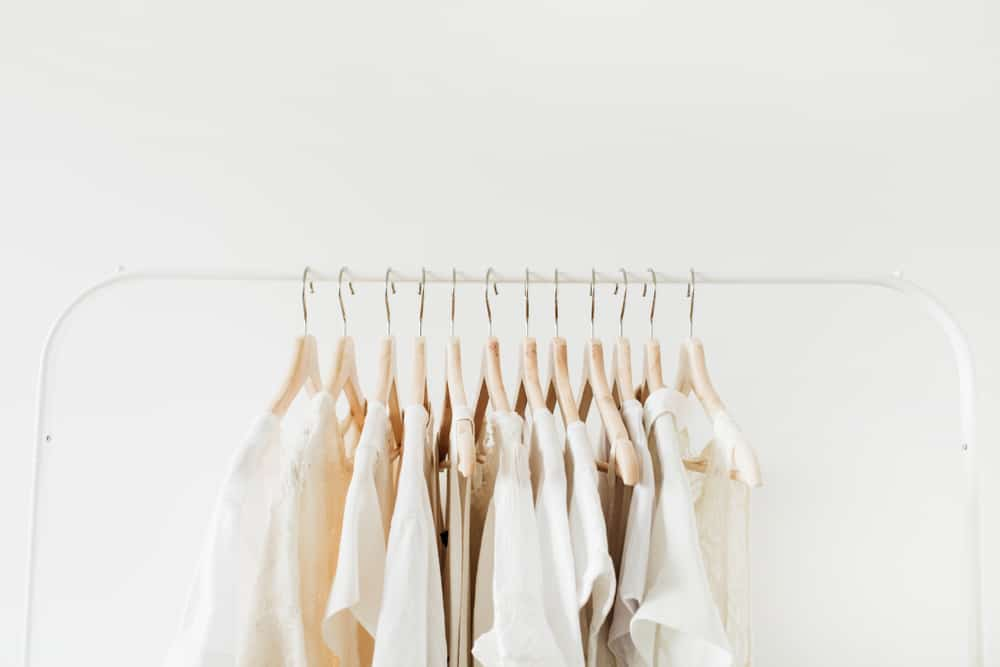 cream-colored blouses on a rack