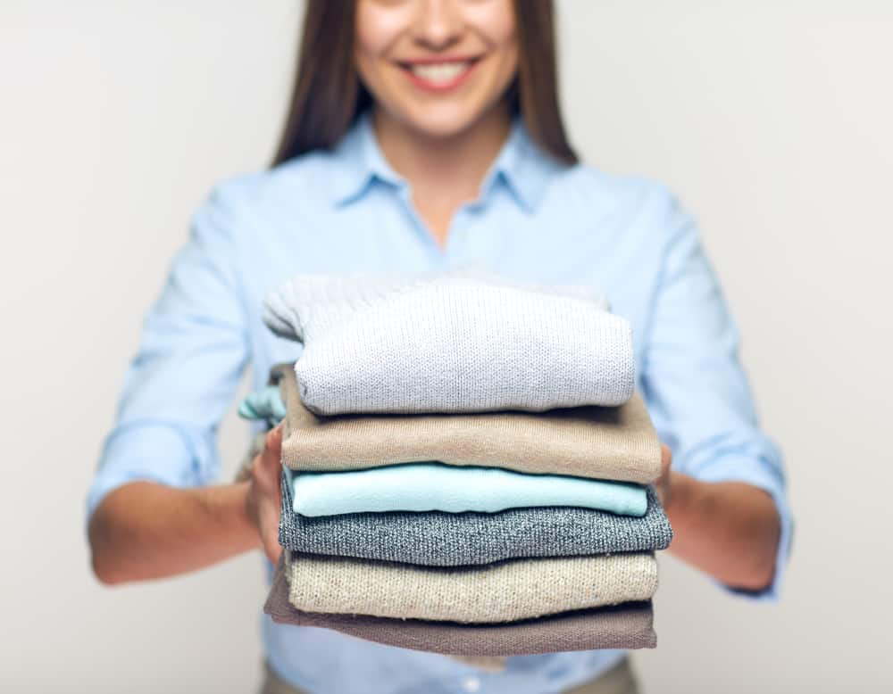 happy woman with folded clothes