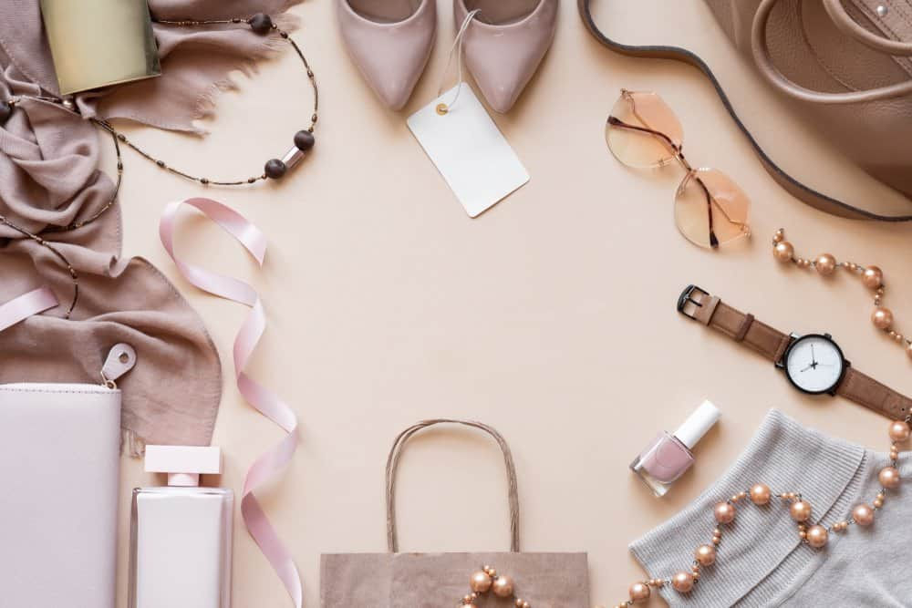 overhead shot of clothes and accessories against beige background
