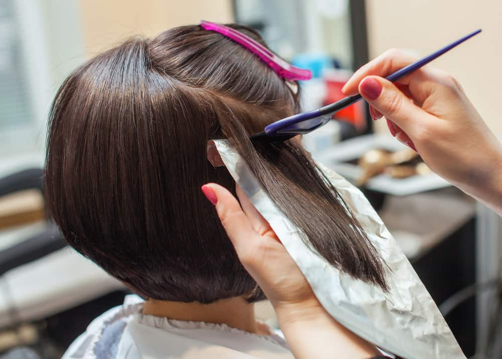 stylist applying bleach to brown hair