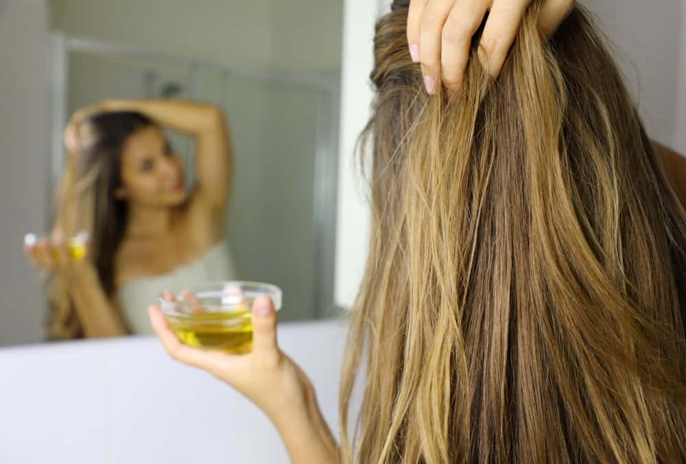 woman applying oil to hair
