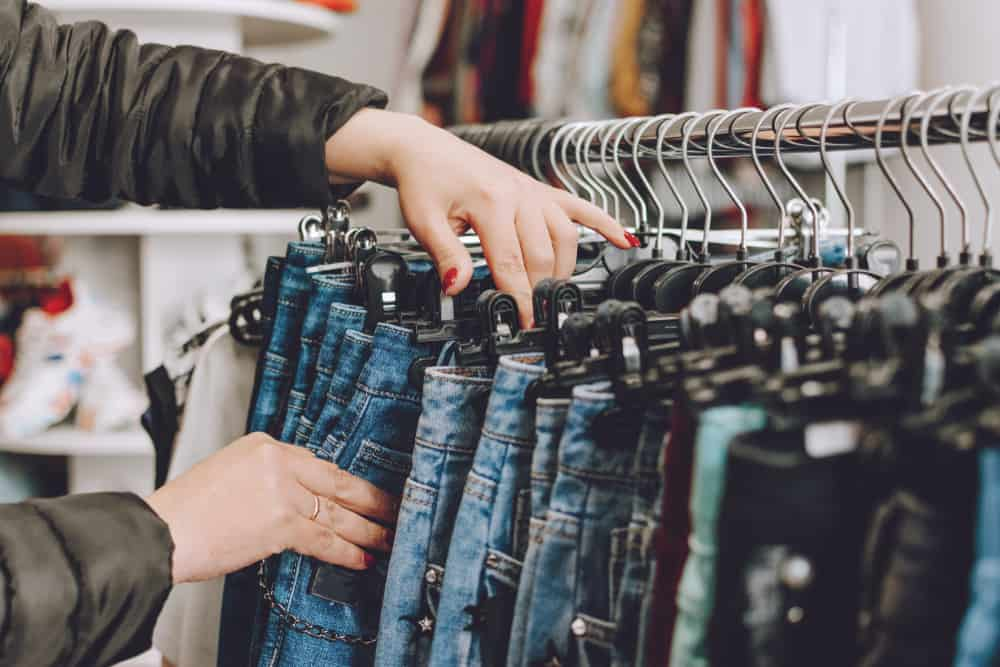 woman browsing jeans on rack