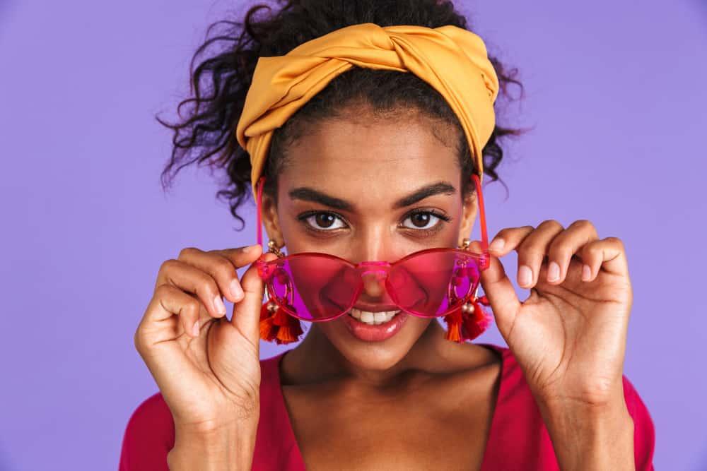 woman with headband pulling back bangs