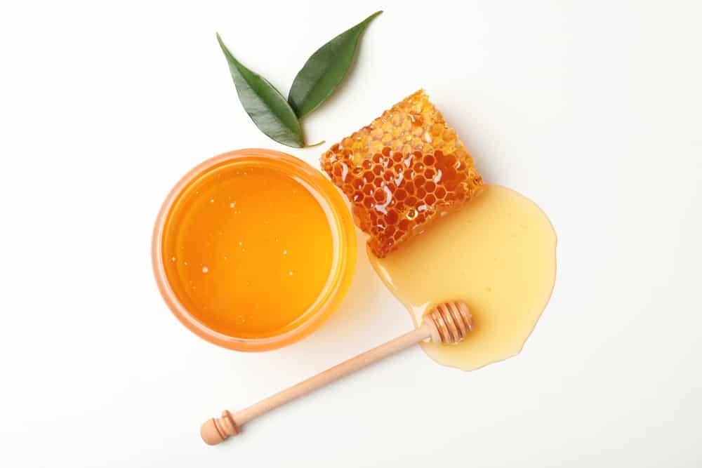 A bowl of honey next to a honeycomb