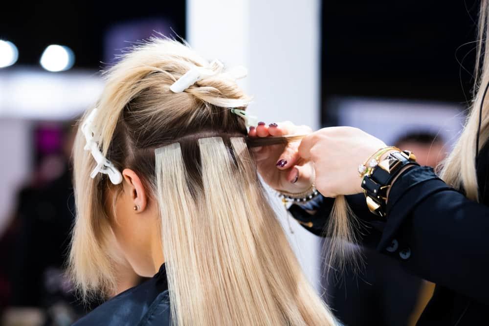 hairdresser applying hair extensions