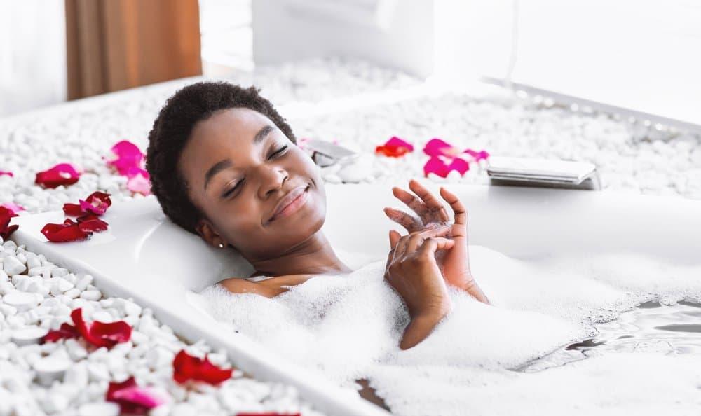 woman smiling bath bubbles flowers
