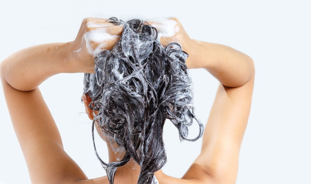 woman with black hair using shampoo