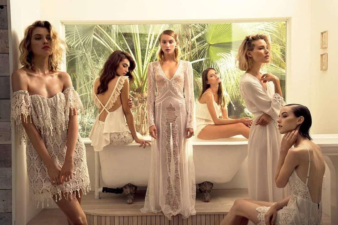 women in white dresses around tub
