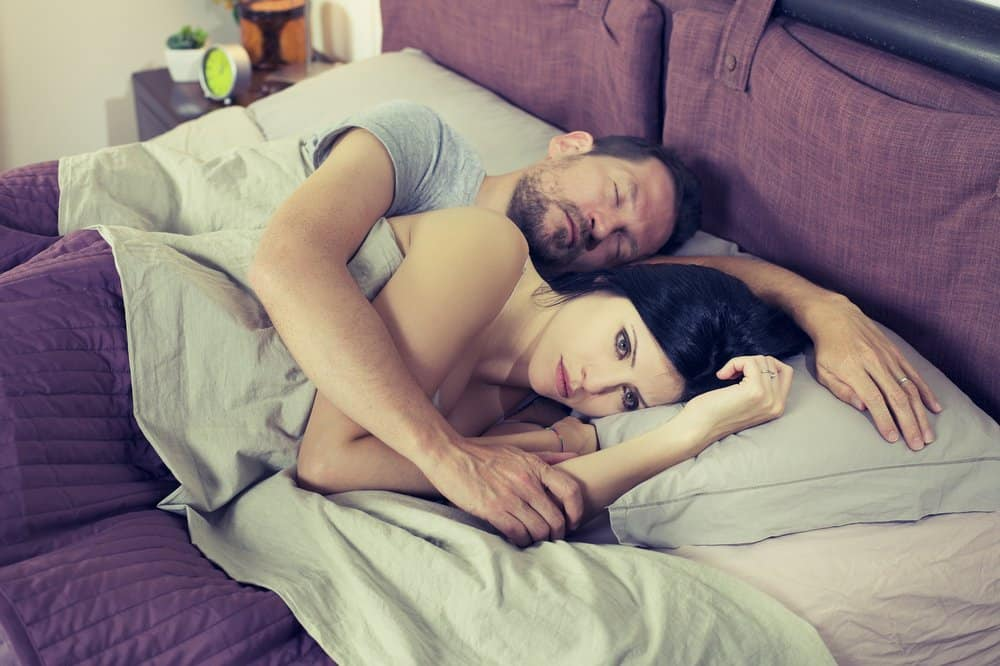 unhappy woman lying in bed beside man