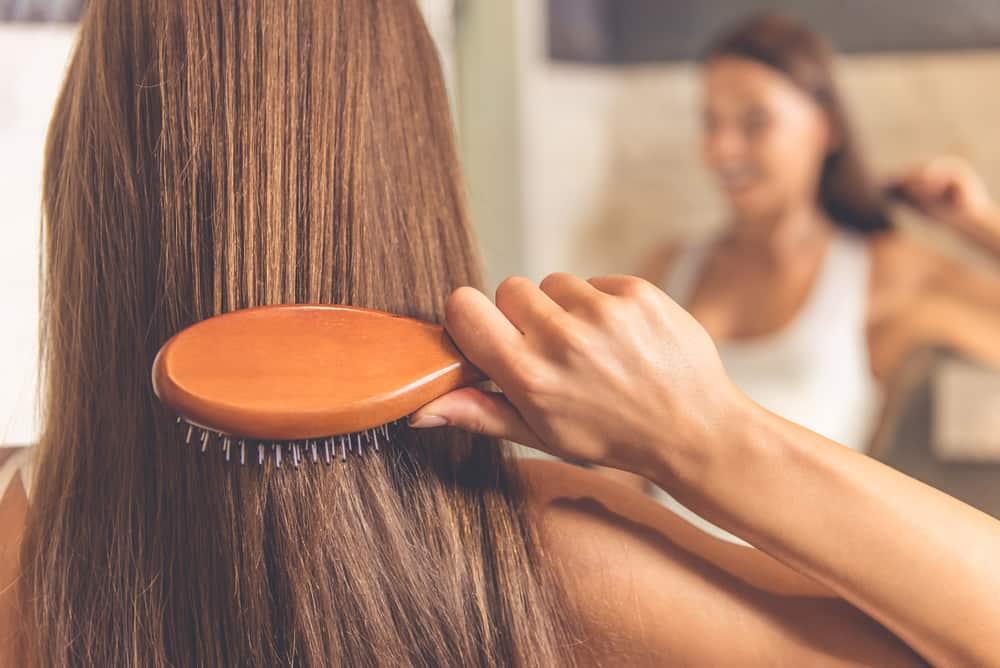 woman brushing through smooth hair