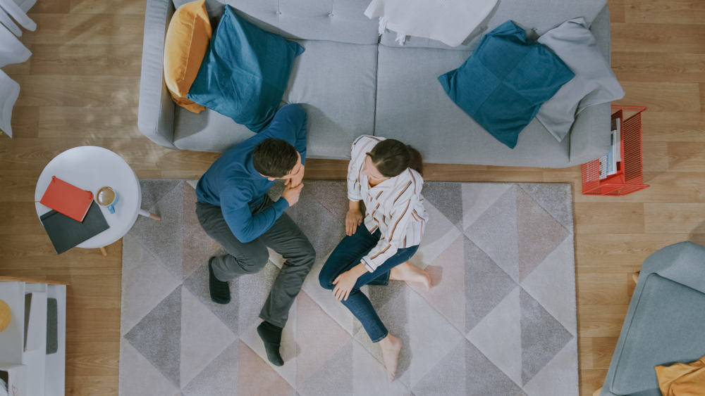young couple sitting on floor talking