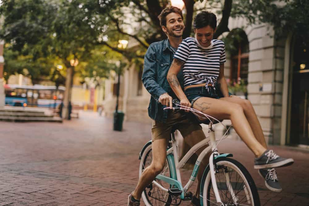a woman sits on the handlebars of a bicycle in front of a smiling man