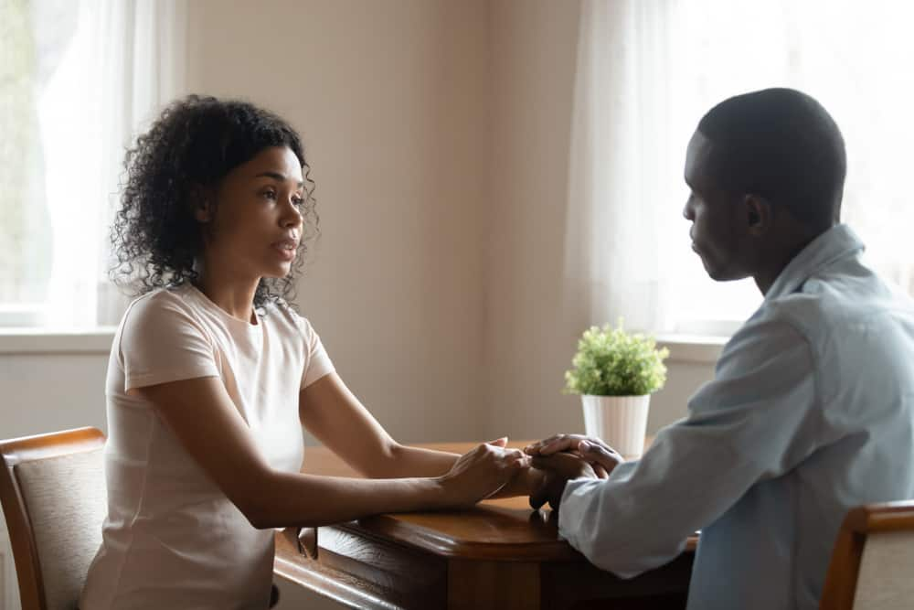 an african-american couple sits holding hands while the woman speaks with a serious expression