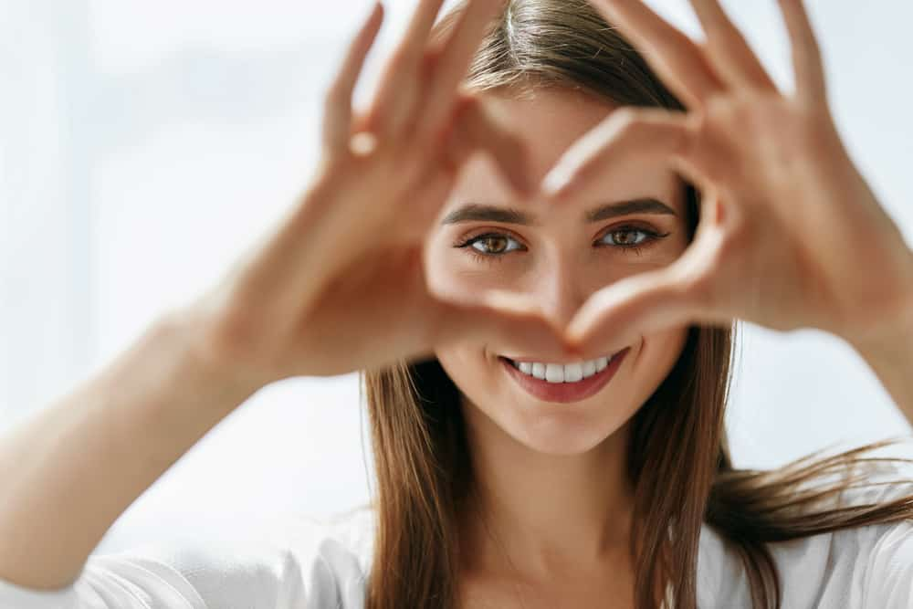 woman making heart-shape with hands