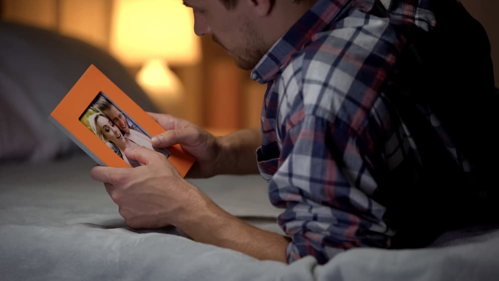 man looking at photograph of couple