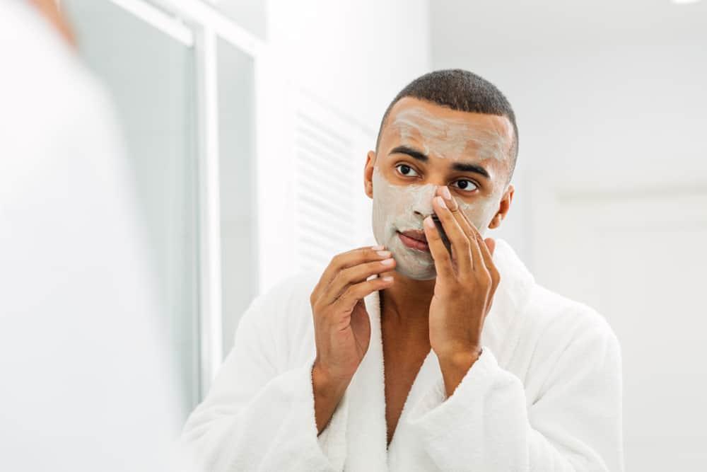 man applying a clay mask
