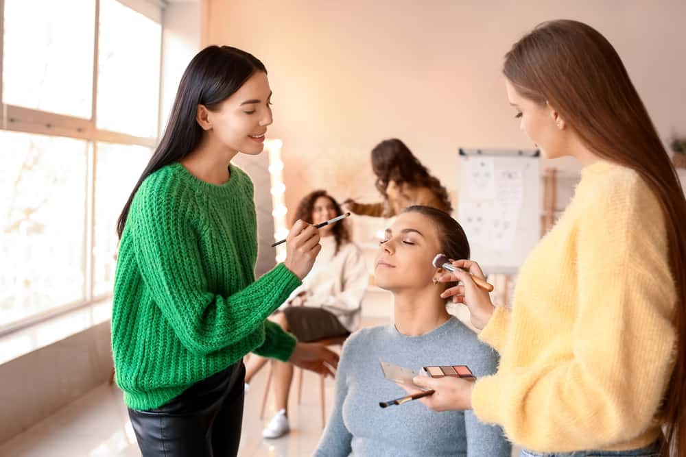 smiling students applying woman's makeup