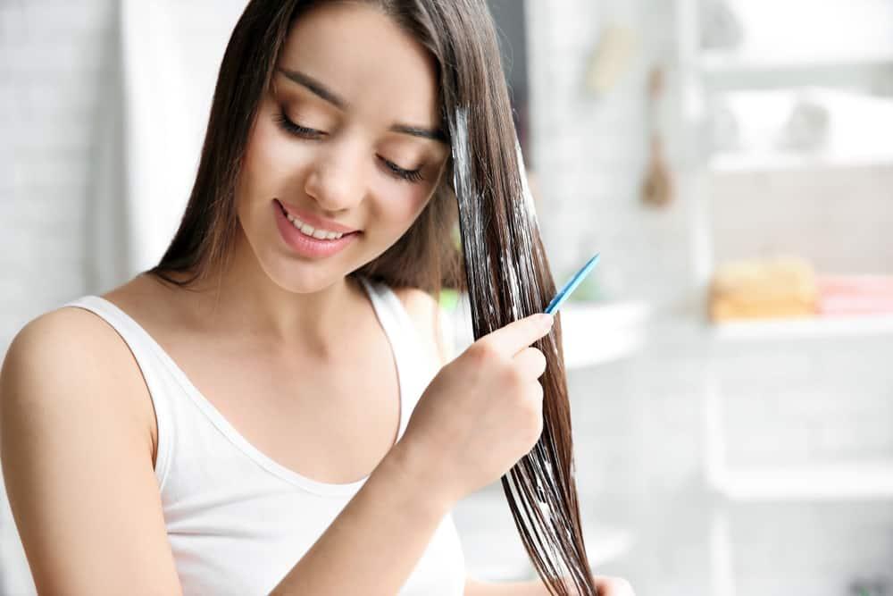 woman brushing hair mask through hair